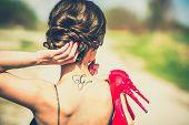 stock photo of red-necked  - Barefoot brunette girl outdoor with red high heels in her hands  - JPG