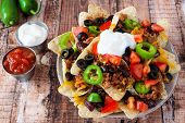 stock photo of jalapeno  - Plate of Mexican nacho chips topped with sour cream ground meat jalapenos tomatoes beans and melted cheese - JPG