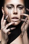 foto of black eyes  - Beautiful girl with creative makeup in Gothic style and the threads of eyes - JPG