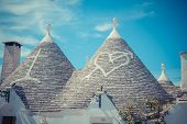 stock photo of conic  - Close up of a conical roofs of a Trulli houses with painted symbols in the southern Italian town of Alberobello - JPG