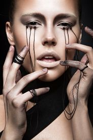 stock photo of gothic girl  - Beautiful girl with creative makeup in Gothic style and the threads of eyes - JPG