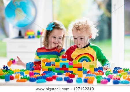 poster of Child playing with colorful toys. Little girl and funny curly baby boy with educational toy blocks. Children play at day care or preschool. Mess in kids room. Toddlers build a tower in kindergarten.