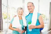Portrait of happy senior couple holding bottle while exercising at home poster