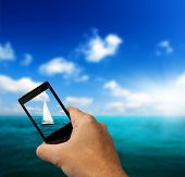 picture of mobile-phone  - sailboat sky and cell phone in hand - JPG