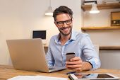 Young happy businessman smiling while reading his smartphone. Portrait of smiling business man readi poster