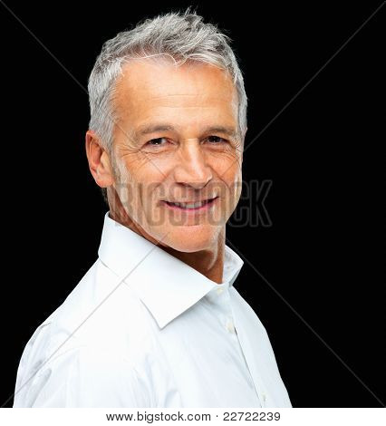 Portrait of charming mature business man smiling over black background