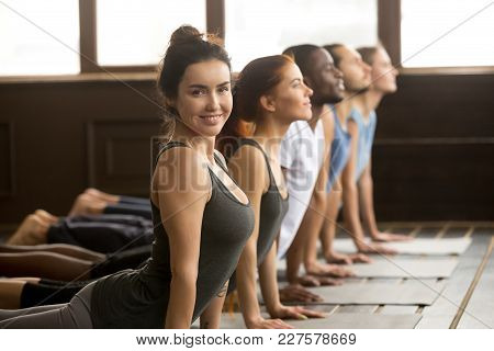 poster of Smiling Yoga Instructor Looking At Camera Doing Fitness Stretching Backbend Exercise Together Teachi