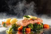 Salmon Steak And Steamed Vegetables On Tray With Steam. poster
