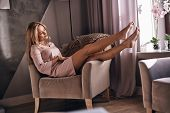 Her Legs Are Perfect.  Attractive Young Woman In Elegant Dress Looking At Her Legs And Smiling While poster