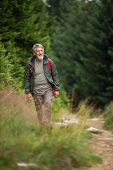 Active senior hiking in high mountains - enjoying his retirement in an active way poster