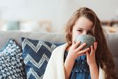 Child Girl Drinking Hot Tea To Recover From Flu. Healing Kids And Protect Immunity From Seasonal Vir poster