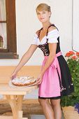 Young woman in dirndl with cake