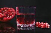 Glass With Pomegranate Juice Pomegranate Seeds And Beautiful Ripe Pomegranate On Black Mirror Backgr poster