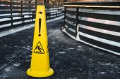 Close Up Shot Of Yellow Warning Sign Stands On Gray Asphalt Covered With Snow, Warns About Wet Road  poster