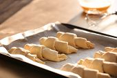 Raw croissants on baking sheet with parchment paper, closeup poster