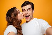 Display of affection of adorable couple girlfrined kissing her man in cheek over yellow background poster
