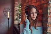 A Sensual Brunette In A Gray Sweater With Headphones Leaning Against A Brick Wall In A Room With Lof poster