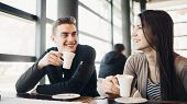 Cheerful Couple Enjoying Coffee Together In Modern Cafe.drinking Hot Caffeine Beverage On A Break Wi poster
