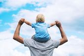 Father Carrying His Son On His Back With Raised Arms Up Against The Sky. Man And Child Boy. Family B poster