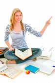 Smiling Teen Girl Sitting On Floor Among Schoolbooks And Pointing In Corner poster