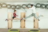 Young Beautiful Fitness Couple Workout Extreme Acrobatic Exercise On Trampoline Jumps As Preparation poster