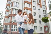 Low Angle Shot Of A Young Happy Family Posing In Front Of New Apartment Building. Father And Mother  poster
