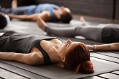 Group Of Young Sporty People Practicing Yoga Lesson Lying In Dead Body Or Corpse Pose, Savasana Exer poster