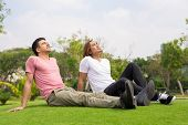 Portrait Of Two Content Handsome Young Men Sunbathing, Relaxing And Sitting On Grass In Park. Relaxa poster
