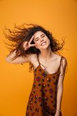 Picture of cute young woman standing isolated over yellow background. Looking camera make peace gest poster