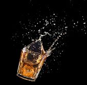 Glass Of Whiskey With Splash Isolated On Black Background. poster