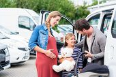 Family buying car, mother, father and child at dealership with soft toy and special kid seat poster