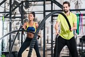 People doing functional training with battle rope in gym poster