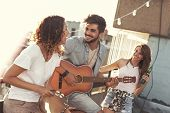 Three Young Friends Having Fun At Rooftop Party, Playing Guitar And Singing. Focus On The Man Playin poster