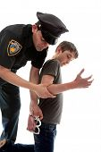 picture of delinquency  - A uniformed policeman arrests and handcuffs a young teen criminal - JPG