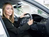 Young Woman Sitting In Right Handed Automobile, Looking At Camera And Smiling In Auto Showroom. Beau poster