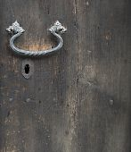 A Metal Forged Door Handle Made Of Black Metal That Is Mounted On A Wooden Door. Below The Handle Is poster