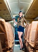 Beautiful Charming Stewardess Dressed In Official Blue Uniform Staying Inside The Plane In Airport.  poster