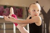 stock photo of leg warmer  - Serious child ballet student looks over her shoulder - JPG