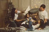 Christmas Time With Family. Happy Young Cheerful Parents Fighting Pillows With Two Daughters. Light  poster