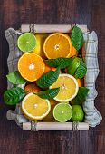 Sliced Citrus In A Basket On A Wooden Table. Flat Lay. Juicy Ripe Slices Of Orange, Lemon And Lime O poster