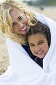 stock photo of mixed race  - A beautiful blond haired blue eyed young woman keeping herself and her young daughter warm in a towel at the beach - JPG
