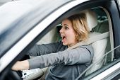 Shocked Young Woman Driver Sitting In Car, Involved In Accident. poster