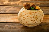 Falafel Balls In A Pita On A Wooden Background. Falafel Is A Traditional Middle Eastern Food, Common poster