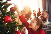 Happy Family Mother, Father And Child Daughter Decorate Christmas Tree At Home poster