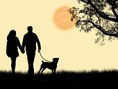 Silhouette Of A Couple Walking Their Dog On Sunset