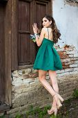 Beautiful Brunette Girl In Glamorous Green Dress And With Beautiful Silver Earrings In Front Of The  poster