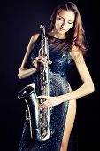 Portrait of a sexual young woman posing with saxophone at studio.