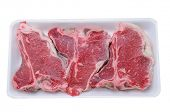 Three t-bone steaks in a foam tray isolated on white.