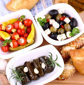 foto of antipasto  - Vine leaves stuffed with peppers and Mediterranean antipasti closeup - JPG