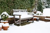 picture of bench  - Snow covered garden bench on a patio in winter - JPG